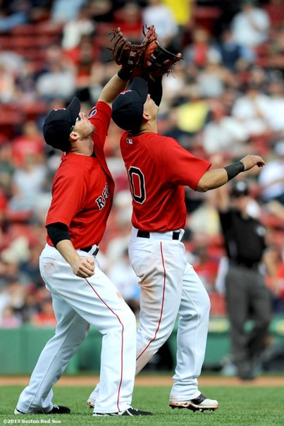 """""""Boston Red Sox shortstop Stephen Drew and third baseman Jose Iglesias collide as Iglesias catches a fly ball during the ninth inning of a game against the Los Angeles Angels of Anaheim Saturday, June 8, 2013 at Fenway Park in Boston, Massachusetts."""""""
