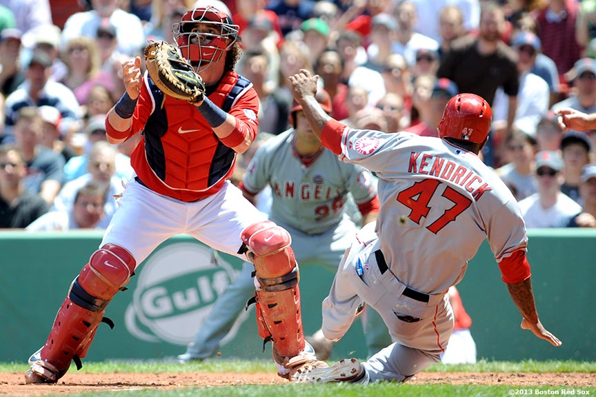 """Boston Red Sox catcher Jarrod Saltalamacchia attempts to tag out second baseman Howie Kendrick during the second nning of a game against the Los Angeles Angels of Anaheim Saturday, June 8, 2013 at Fenway Park in Boston, Massachusetts."""