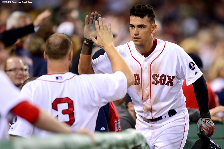 """Boston Red Sox third baseman Jose Iglesias high fives teammates after scoring in the sixth inning of a game against the Los Angeles Angels of Anaheim Saturday, June 8, 2013 at Fenway Park in Boston, Massachusetts."""