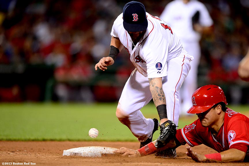 """Boston Red Sox first baseman loses the ball as he applies a tag to catcher Hank Conger on a pickoff during the seventh inning of a game against the Los Angeles Angels of Anaheim Saturday, June 8, 2013 at Fenway Park in Boston, Massachusetts."""