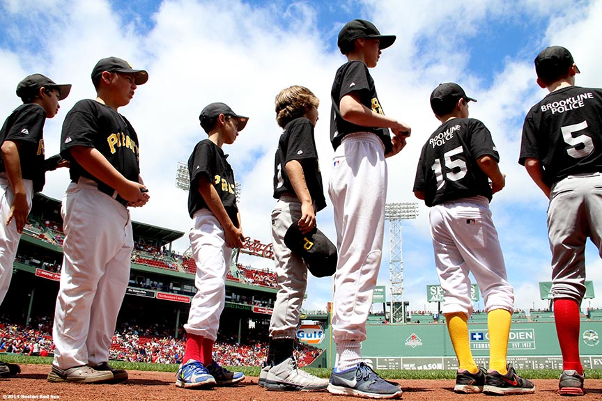 """Brookline little league players prepare to take the field for a pre-game ceremony before a game between the Boston Red Sox and the Los Angeles Angels of Anaheim Saturday, June 8, 2013 at Fenway Park in Boston, Massachusetts."""