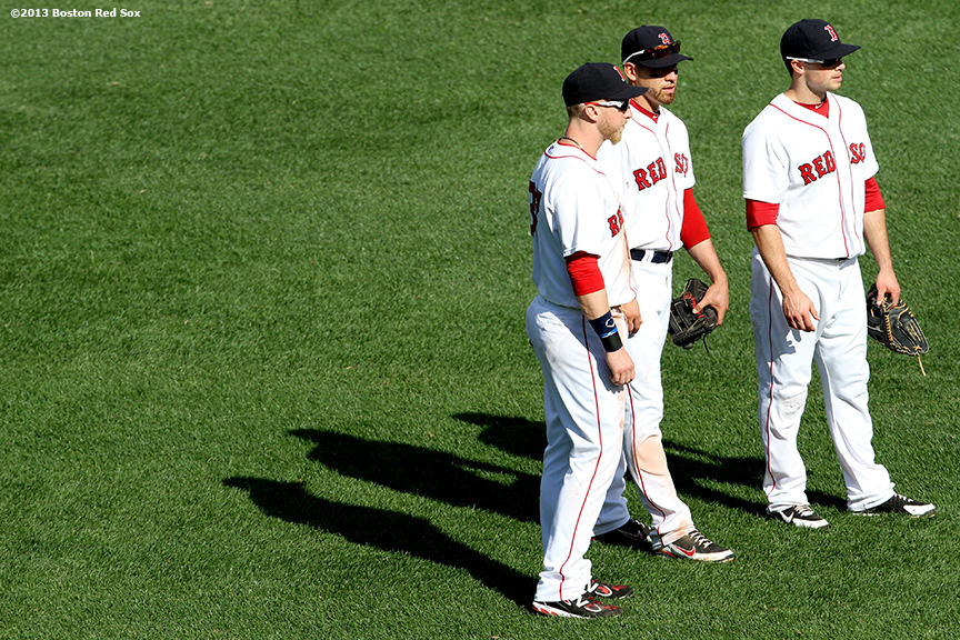 """Boston Red Sox outfielders Mike Carp (left), Jacoby Ellsbury (center), and Daniel Nava (right) meet during a pitching change in the  eighth inning of a game against the Los Angeles Angels of Anaheim Sunday, June 9, 2013 at Fenway Park in Boston, Massachusetts."""