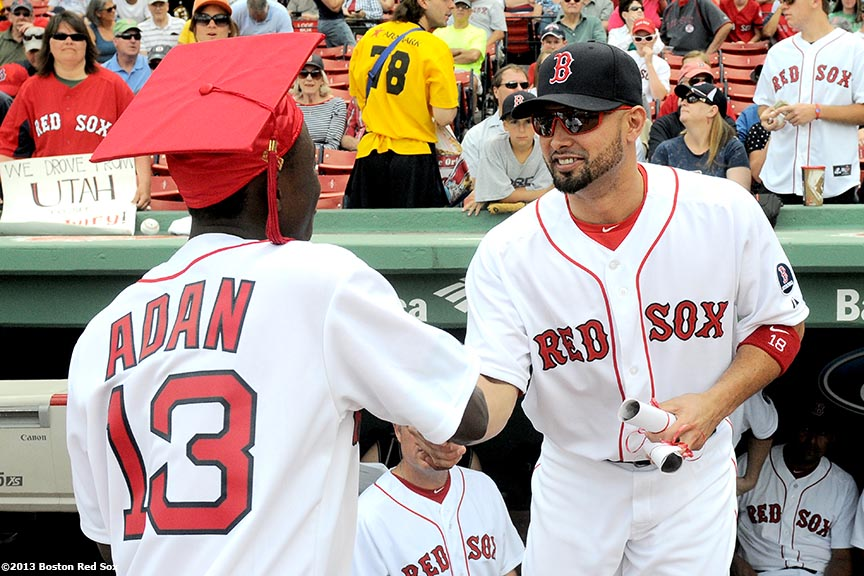 """Boston Red Sox outfielder Shane Victorino congratulates a Red Sox graduating Scholar during a pre-game ceremony Sunday, June 10, 2013 at Fenway Park in Boston, Massachusetts."""