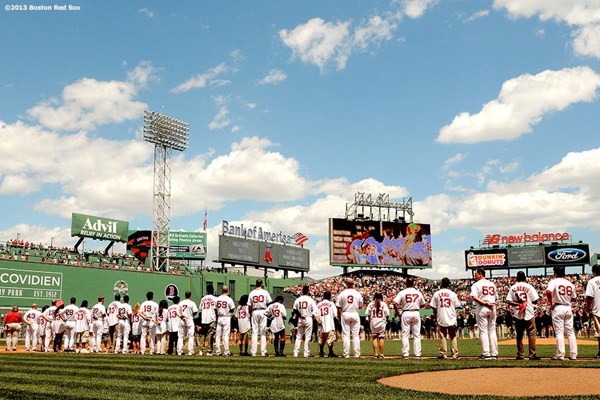 """The graduating class of Boston Red Sox scholars line up alongside Red Sox players during a pre-game ceremony Sunday, June 10, 2013 at Fenway Park in Boston, Massachusetts."""