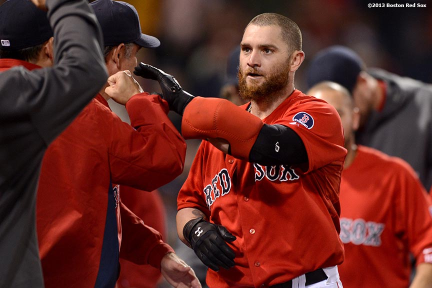 """""""Boston Red Sox outfielder Jonny Gomes high fives teammates after hitting a walk-off two-run home run in the bottom of the ninth inning to defeat the Tampa Bay Rays 3-1 Tuesday, June 18, 2013 at Fenway Park in Boston, Massachusetts."""""""
