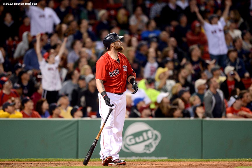 """Boston Red Sox outfielder Jonny Gomes follows through after hitting a walk-off two-run home run in the bottom of the ninth inning to defeat the Tampa Bay Rays 3-1 Tuesday, June 18, 2013 at Fenway Park in Boston, Massachusetts."""
