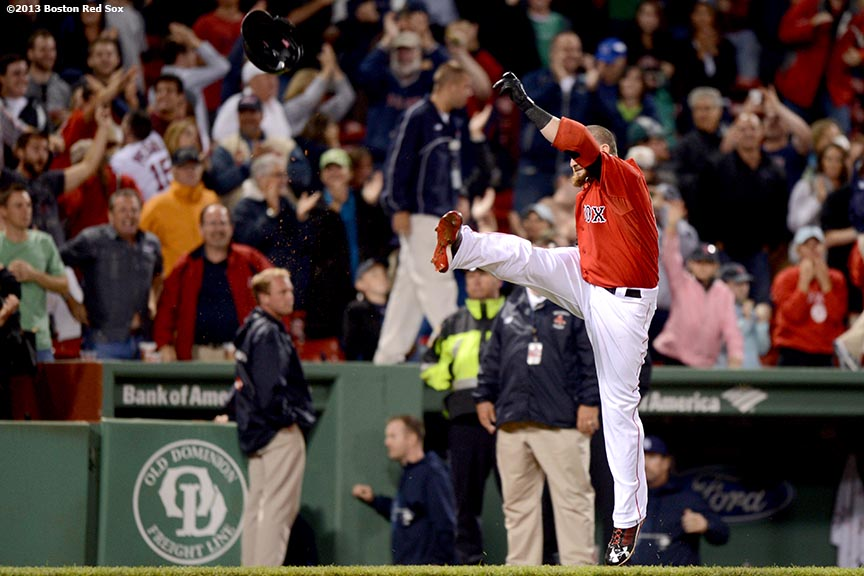 """Boston Red Sox outfielder Jonny Gomes punts his helmet as he runs toward home plate after hitting a walk-off two-run home run in the bottom of the ninth inning to defeat the Tampa Bay Rays 3-1 Tuesday, June 18, 2013 at Fenway Park in Boston, Massachusetts."""