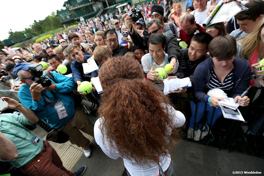"""Serena Williams signs autographs for fans at the All England Lawn and Tennis Club in London, England Wednesday, June 26, 2013 during the 2013 Championships Wimbledon."""