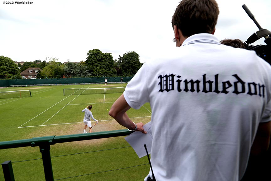 """A reporter watches as Andy Murray practices at the All England Lawn and Tennis Club in London, England Thursday, June 27, 2013 during the 2013 Championships Wimbledon."""