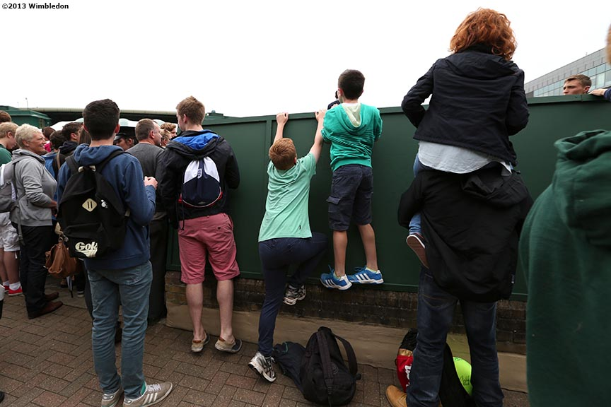"""Young fans climb a wall to get a better view of No. 14 Court at the All England Lawn and Tennis Club in London, England Friday, June 28, 2013 during the 2013 Championships Wimbledon."""