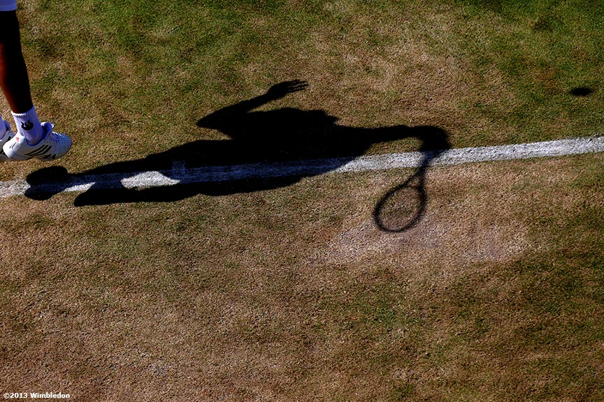 """The shadow of Ivan Dodig is shown as he serves at the All England Lawn and Tennis Club in London, England Wimbledon, June 29, 2013 during the 2013 Championships Wimbledon."""