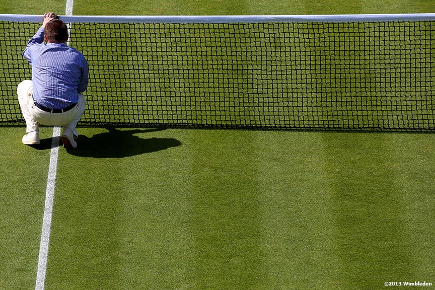 """An umpire measures the height of the net at the All England Lawn and Tennis Club in London, England Wimbledon, June 29, 2013 during the 2013 Championships Wimbledon."""
