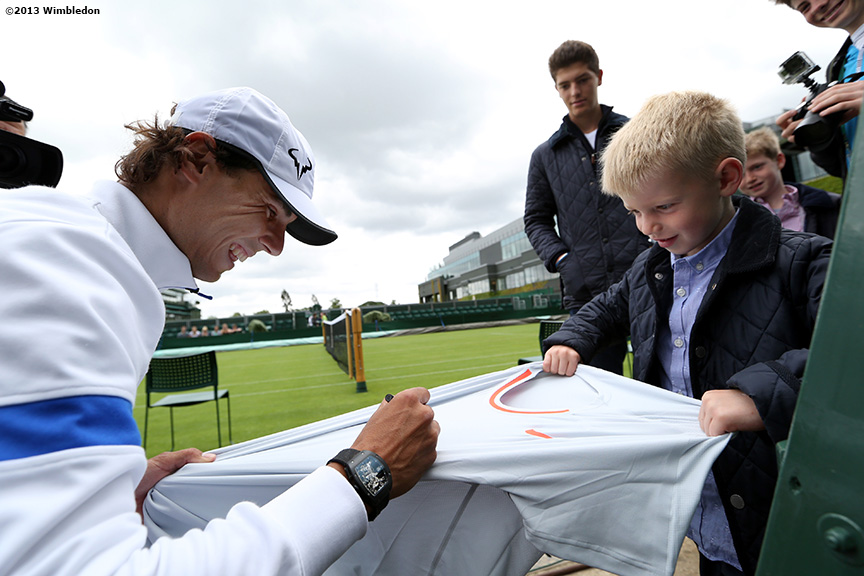 """Rafael Nadal signs an autograph after a practice session at the All England Lawn and Tennis Club in London, England Saturday, June 22, 2013 before the start of the 2013 Championships Wimbledon."""