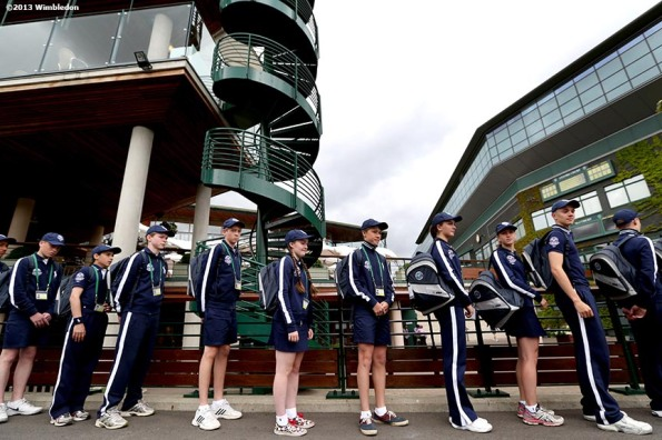 """A group of ball boys and ball girls stand in line at the All England Lawn and Tennis Club in London, England Saturday, June 22, 2013 before the start of the 2013 Championships Wimbledon."""