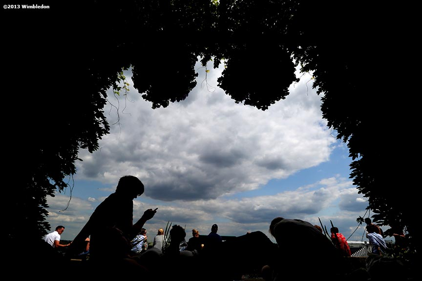 """Fans sit beneath flowers on Henman Hill at the All England Lawn and Tennis Club in London, England Tuesday, June 25, 2013 during the 2013 Championships Wimbledon."""