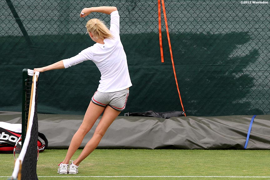 """Urszula Radwanska stretches at the Aorangi Practice Courts at the All England Lawn and Tennis Club in London, England Monday, June 24, 2013 during the 2013 Championships Wimbledon."""