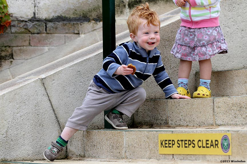 """A boy plays on the steps at the All England Lawn and Tennis Club in London, England Monday, June 24, 2013 during the 2013 Championships Wimbledon."""