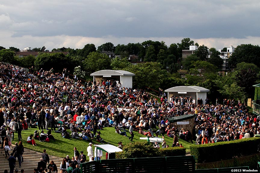 """Fans sit on Henman Hill as they watch a match between Andy Murray and Benjamin Becker on the big screen at the All England Lawn and Tennis Club in London, England Monday, June 24, 2013 during the 2013 Championships Wimbledon."""