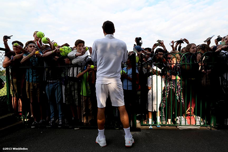 """Roger Federer signs autographs at the Aorangi practice courts at the All England Lawn and Tennis Club in London, England Tuesday, June 25, 2013 during the 2013 Championships Wimbledon."""