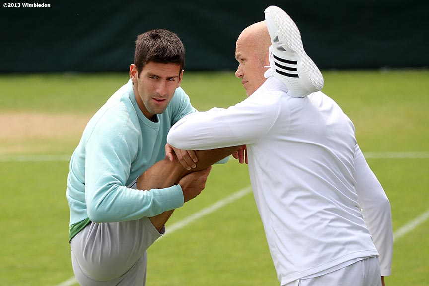 """Novak Djokovic stretches before a practice session at the All England Lawn and Tennis Club in London, England Wednesday, June 26, 2013 during the 2013 Championships Wimbledon."""