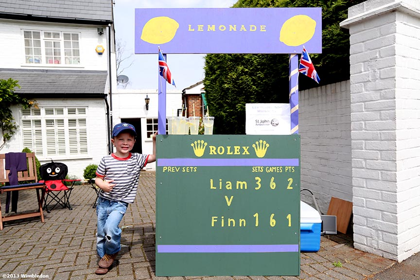 """Liam Stephan, three, poses next to his lemonade stand"