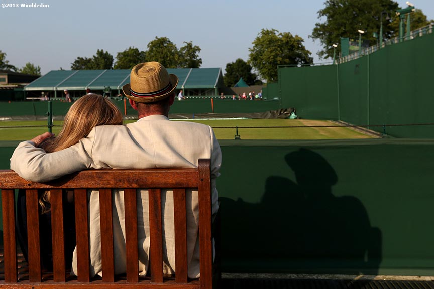 """Guests sit near the outer courts as the sun sets at the All England Lawn and Tennis Club in London, England Tuesday, July 2, 2013 during the 2013 Championships Wimbledon."""