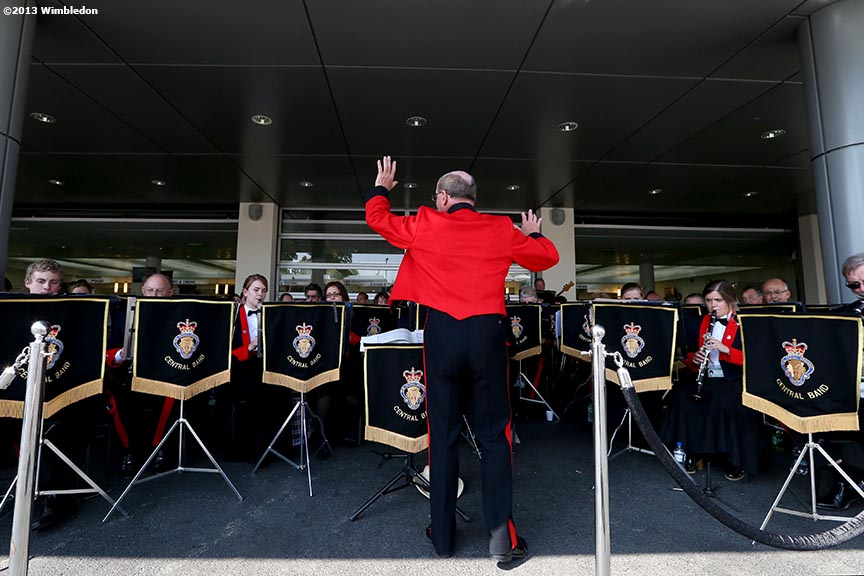 """A conductor leads the flagship band of the Royal British Legion at the All England Lawn and Tennis Club in London, England Sunday, July 6, 2013 during the 2013 Championships Wimbledon."""