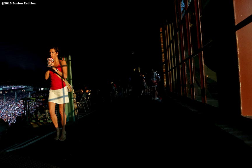 """A woman walks through the concourse during a game between the Boston Red Sox and the New York Yankees Friday, July 19, 2013 at Fenway Park in Boston, Massachusetts."""