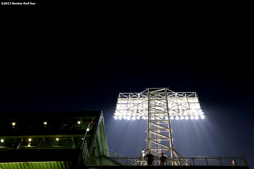 """Fans stand under a stadium light during a game between the Boston Red Sox and the New York Yankees Friday, July 19, 2013 at Fenway Park in Boston, Massachusetts."""