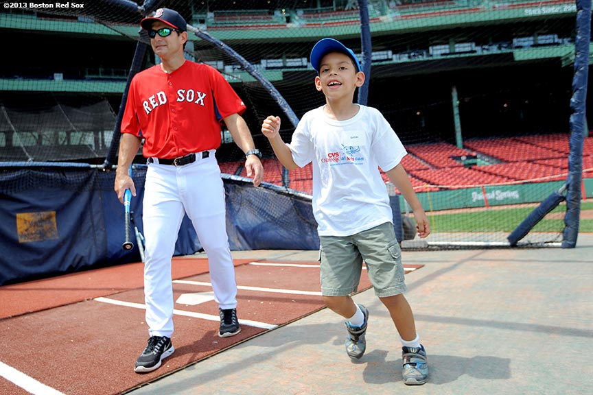 """Boston Red Sox hitting coach Greg Colbrunn exits the batting cage as a CVS Hitting Clinic participant celebrates after taking batting practice at Fenway Park in Boston, Massachusetts Monday, July 22, 2013."""