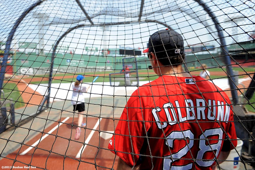 """Boston Red Sox hitting coach Greg Colbrunn watches as a CVS Hitting Clinic participant takes batting practice on the field at Fenway Park in Boston, Massachusetts Monday, July 22, 2013."""