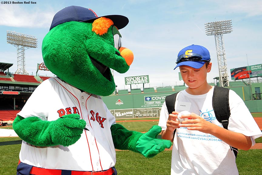 """Boston Red Sox mascot Wally the Green Monster signs an autograph for a CVS Hitting Clinic participant after taking batting practice on the field at Fenway Park in Boston, Massachusetts Monday, July 22, 2013."""