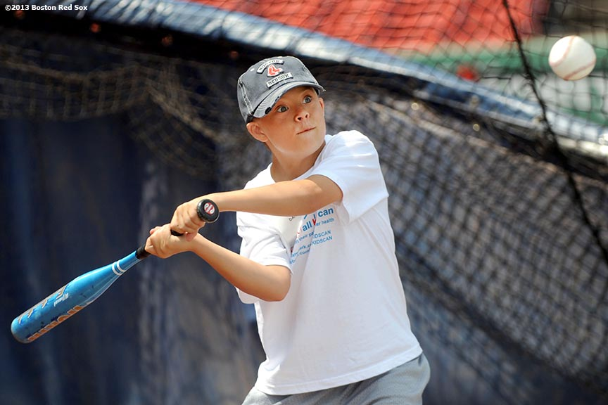 """A Boston Red Sox CVS Hitting Clinic participant takes batting practice on the field at Fenway Park in Boston, Massachusetts Monday, July 22, 2013."""