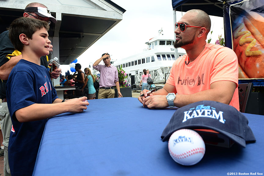 """Boston Red Sox outfielder Shane Victorino signs autographs during a National Hot Dog Day tasting contest sponsored by Kayem Franks at the Landing at Long Wharf in Boston, Massachusetts Tuesday, July 23, 2013."""