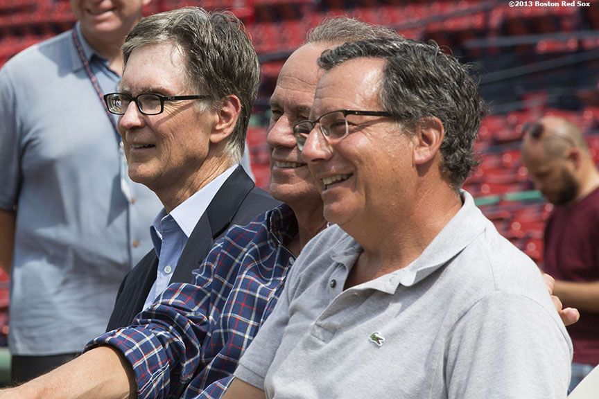 """(From left) Boston Red Sox Principal Owner John Henry, President & CEO Larry Lucchino, and Chairman Tom Werner watch as Dustin Pedroia addresses the media at Fenway Park in Boston, Massachusetts during a press conference Wednesday, July 24, 2013 announcing an eight-year contract extension continuing through the 2021 season."""