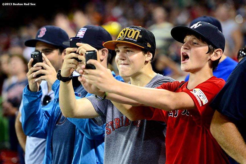 """""""Fans take photographs during a rain delay in the eighth inning of a game between the Boston Red Sox and the Tampa Bay Rays Monday, July 29, 2013 at Fenway Park in Boston, Massachusetts."""""""