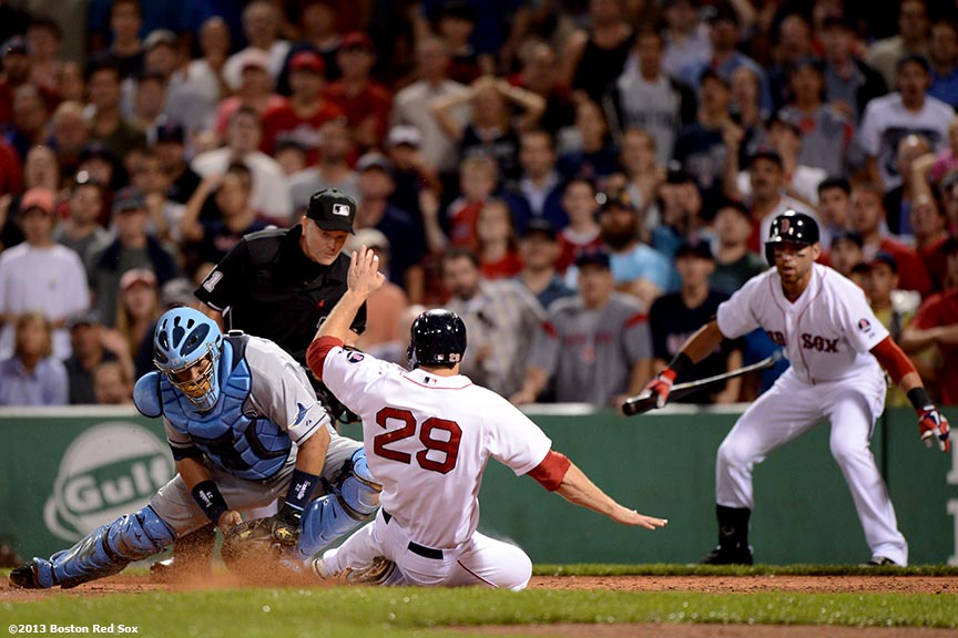 """Boston Red Sox outfielder Daniel Nava is tagged out at home plate by catcher Jose Molina after attempting to score on a sacrifice fly during the eighth inning of a game against the Tampa Bay Rays Monday, July 29, 2013 at Fenway Park in Boston, Massachusetts."""