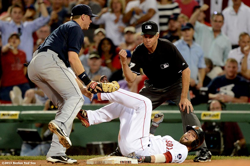 """Boston Red Sox second baseman Dustin Pedroia dives back to first base after getting caught in a rundown during the fourth inning of a game against the Seattle Mariners Tuesday, July 30, 2013 at Fenway Park in Boston, Massachusetts."""