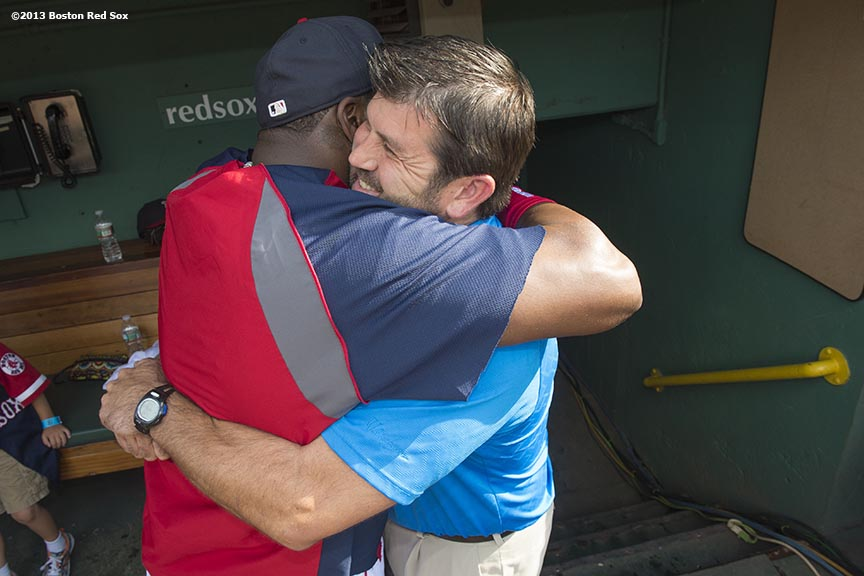 """Former Boston Red Sox catcher Jason Varitek hugs designated hitter David Ortiz in the dugout before a game against the Seattle Mariners Tuesday, July 30, 2013 at Fenway Park in Boston, Massachusetts."""