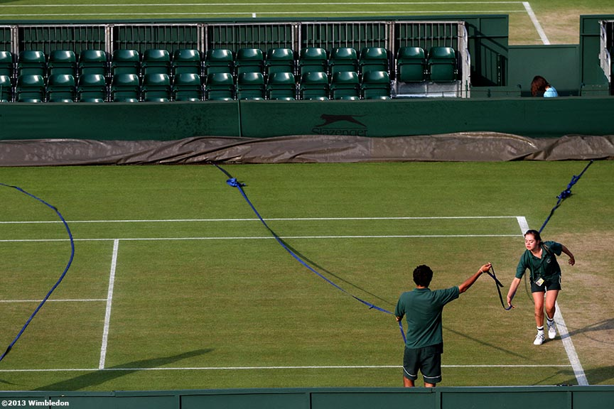 """Grounds Crew members prepare to pull a cover over a court at the All England Lawn and Tennis Club in London, England Tuesday, July 2, 2013 during the 2013 Championships Wimbledon."""