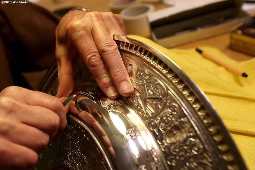 """Roman Zoltawski, official All England Club trophy engraver, inspects the Venus-Rosewater Dish before the Ladies' Championship Match on Centre Court at the All England Lawn and Tennis Club in London, England Saturday, July 6, 2013 during the 2013 Championships Wimbledon."""