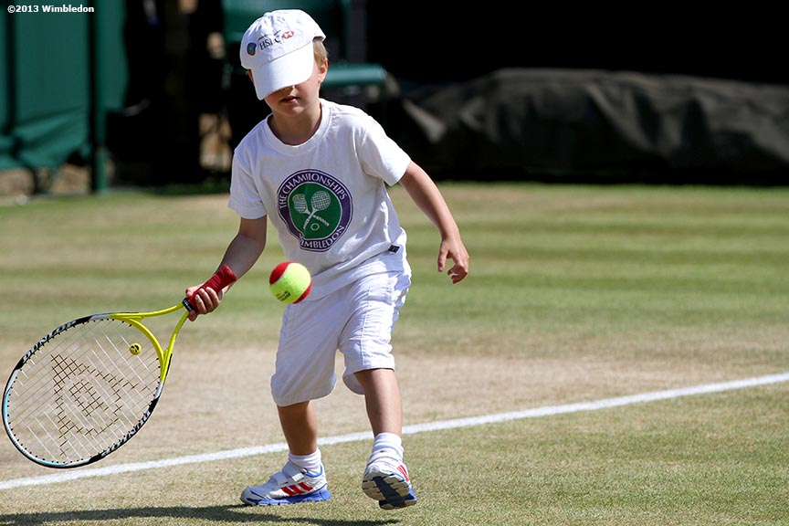"""A young boy plays tennis at the All England Lawn and Tennis Club in London, England Sunday, July 6, 2013 during the 2013 Championships Wimbledon."""