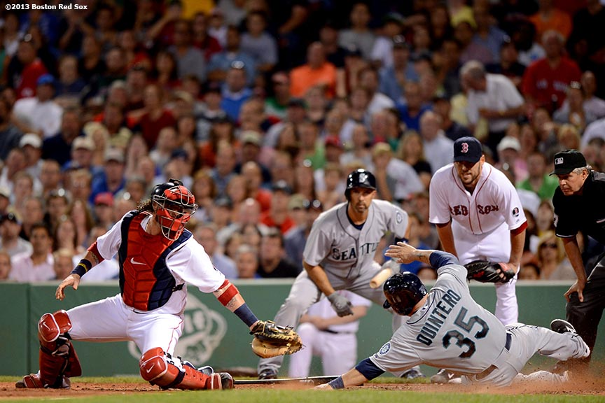 """Boston Red Sox catcher Jarrod Saltalamacchia attempts to tag out catcher Humberto Quintero at home plate during the sixth inning of a game against the the Seattle Mariners Wednesday, July 31, 2013 at Fenway Park in Boston, Massachusetts."""