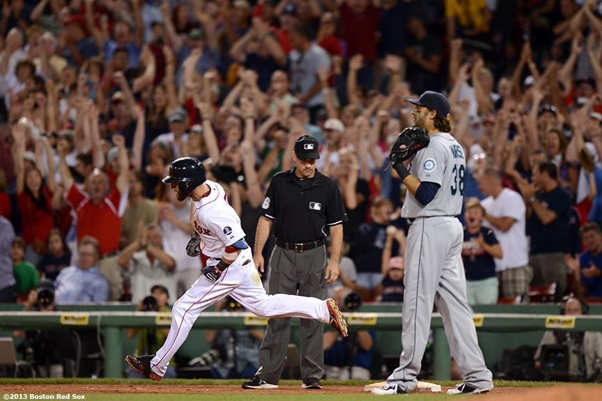 """Boston Red Sox second baseman Dustin Pedroia rounds first base after a two-run home run during to give the Red sox a 4-3 lead during the seventh inning of a game against the Seattle Mariners Wednesday, July 31, 2013 at Fenway Park in Boston, Massachusetts."""