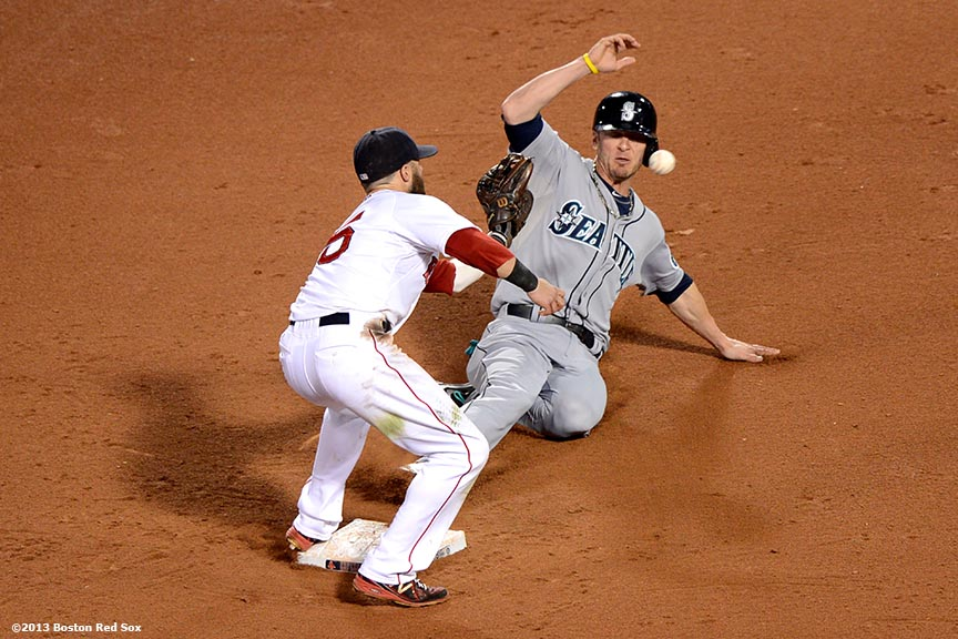 """Boston Red Sox second baseman Dustin Pedroia applies a tag on Brendan Ryan at second base during the twelfth inning of a game against the Seattle Mariners Wednesday, July 31, 2013 at Fenway Park in Boston, Massachusetts."""