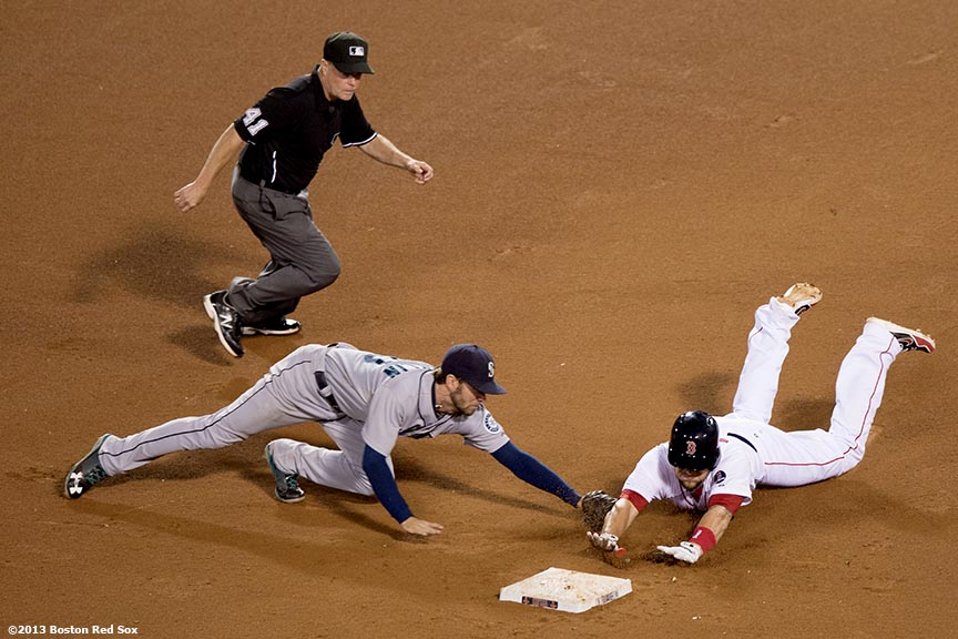 """Boston Red Sox third baseman Brandon Snyder slides into second base and evades a tag by second baseman Nick Franklin during the fourteenth inning of a game against the Seattle Mariners Wednesday, July 31, 2013 at Fenway Park in Boston, Massachusetts."""