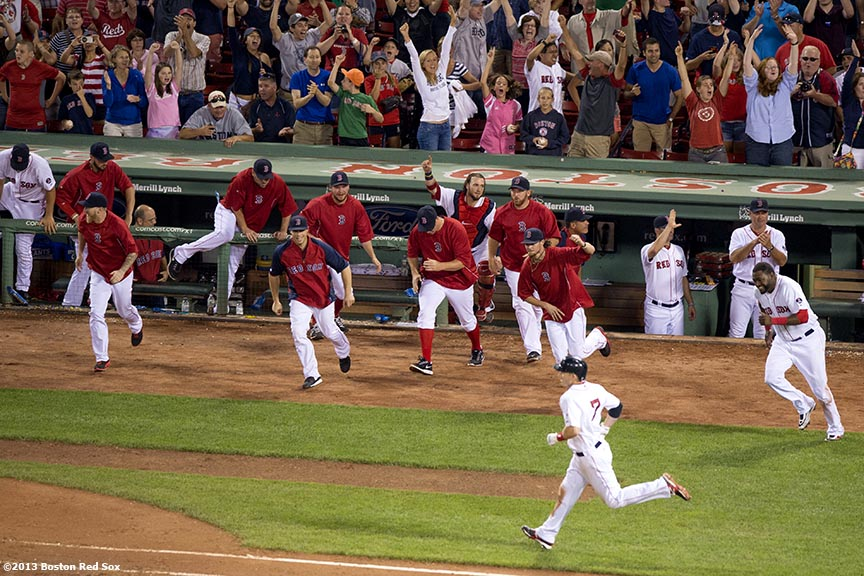 """Boston Red Sox teammates celebrate as shortstop Stephen Drew runs to first base after hitting the game winning RBI single with the bases loaded during the bottom of the fifteenth inning of a game against the Seattle Mariners Thursday, August 1, 2013 at Fenway Park in Boston, Massachusetts."""