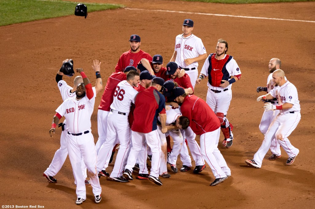 """Boston Red Sox teammates mob shortstop Stephen Drew after Drew hits a game winning RBI single with the bases loaded during the bottom of the fifteenth inning of a game against the Seattle Mariners Thursday, August 1, 2013 at Fenway Park in Boston, Massachusetts."""