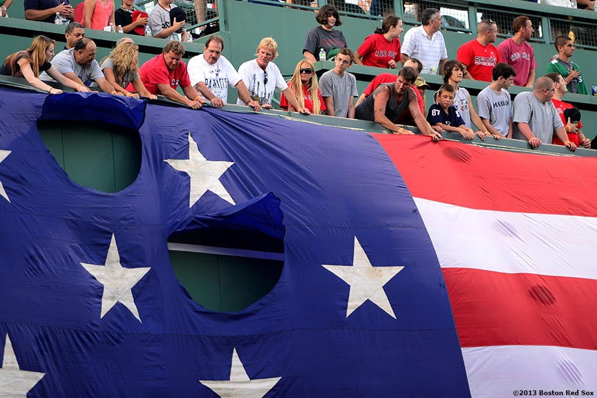 """Fans help drop the American flag over the Green Monster during a Military appreciation ceremony before a game between the Boston Red Sox and the Seattle Mariners Wednesday, July 31, 2013 at Fenway Park in Boston, Massachusetts."""