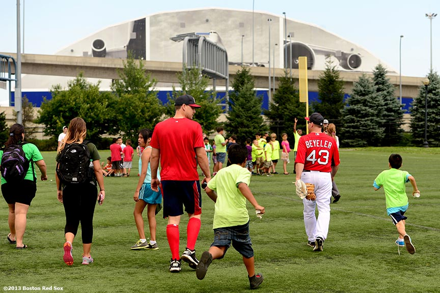 """Boston Red Sox first base coach Arnie Beyeler and catcher Ryan Lavarnway give instructions during an out fielding clinic at East Boston Stadium in East Boston, Massachusetts Thursday, August 1, 2013 as part of the Boston Parks & Recreation Department's Sox Talk program."""